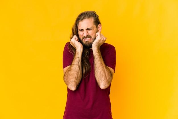 Молодой человек с длинными волосами смотрит, закрывая уши руками.