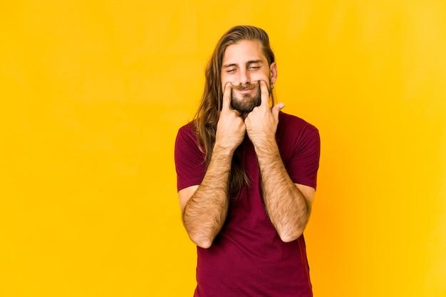 Молодой человек с длинными волосами сомневается в двух вариантах.