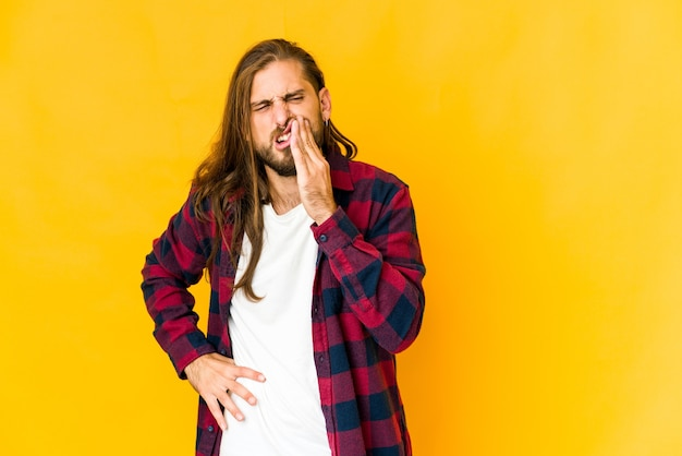 長い髪の若い男は、強い歯の痛み、臼歯の痛みを持っています。
