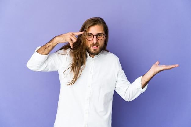 긴 머리를 가진 젊은 남자 잡고 손에 제품을 보여주는 모습.