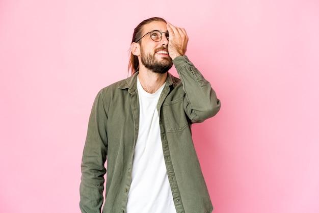 긴 머리를 가진 젊은 남자는 행복하고 평온하고 자연스러운 감정을 웃고 있습니다.