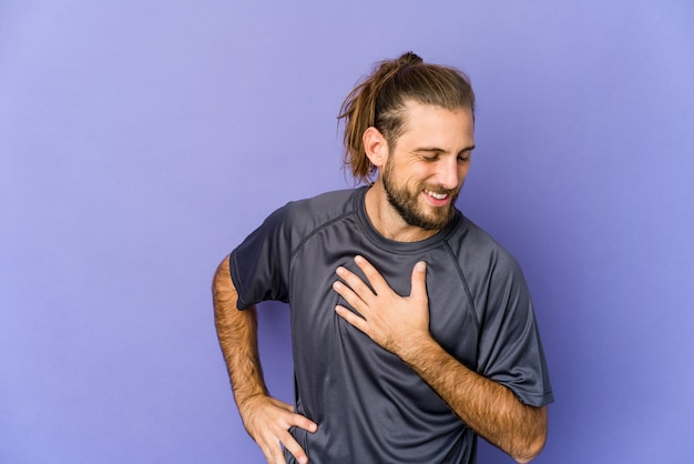 Young man with long hair look laughing keeping hands on heart, concept of happiness.