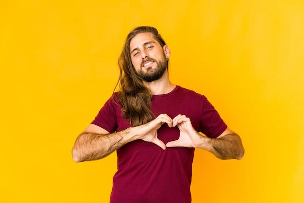 Молодой человек с длинными волосами выглядит улыбаясь и показывает форму сердца руками.