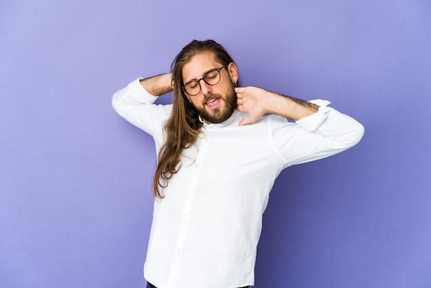 긴 머리를 가진 젊은 남자는 팔을 스트레칭, 편안한 자세를 본다.