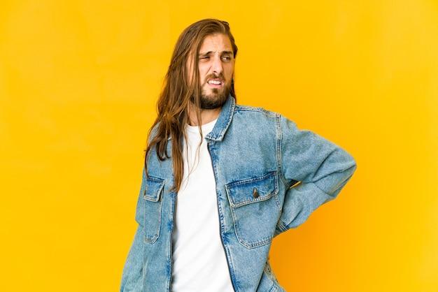 긴 머리를 가진 젊은 남자는 허리 통증을 겪고 있습니다.