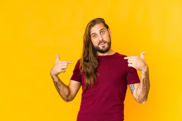 긴 머리를 가진 젊은 남자는 넓게 웃고 손가락으로 가리키는 놀란 표정.