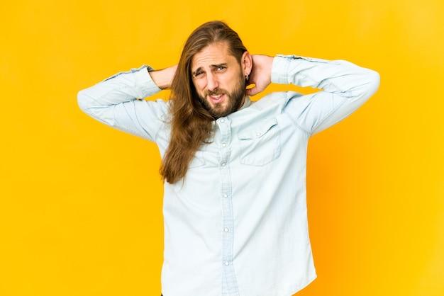 긴 머리를 가진 젊은 남자는 머리 뒤를 만지고 생각하고 선택합니다.