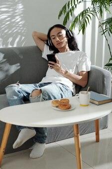 新しい曲を聴いたり、スマートフォンでミュージックビデオを見たりソファでリラックスした長い髪の若い男
