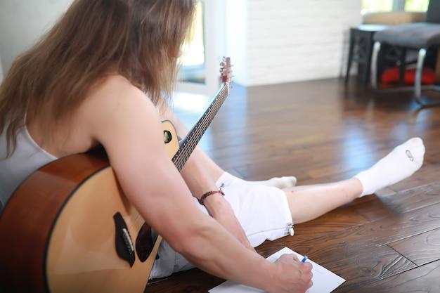 어쿠스틱 기타와 긴 머리를 가진 젊은 남자