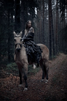 Young man with long hair with horse in dark forest.