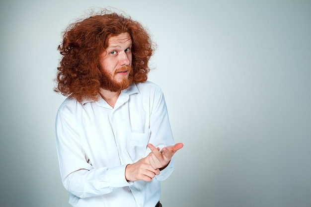 Young man with long red hair looking at camera counting on fingers