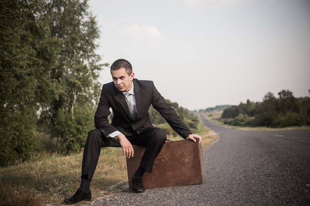 Young man with luggage on  road