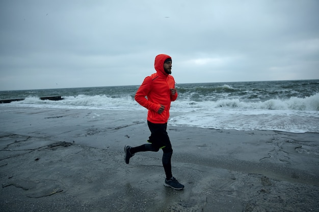 Young man with lush beard training on beach in cold early morning, wearing black sporty clothes and warm orange coat with hood while jogging. fitness and sport concept