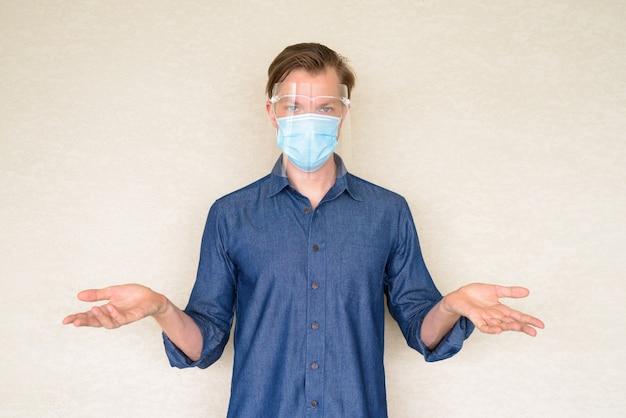 コンクリートの壁に肩をすくめマスクと顔のシールドを持つ若者