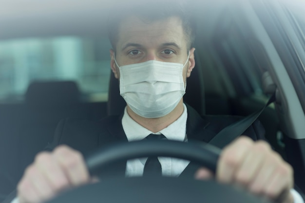 Young man with mask driving
