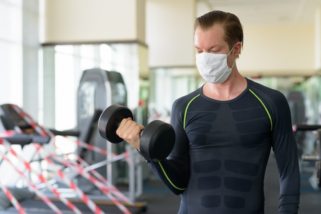 コロナウイルスcovid-19中にジムでダンベル運動のマスクを持つ若者