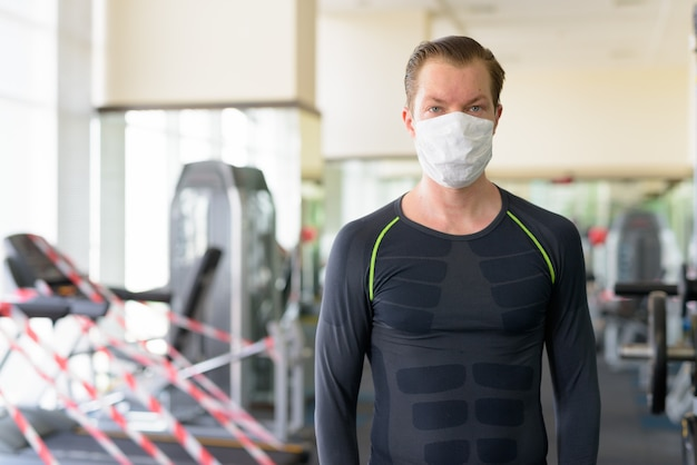 コロナウイルスcovid-19中にジムでコロナウイルスの発生から保護するためのマスクを持つ若い男