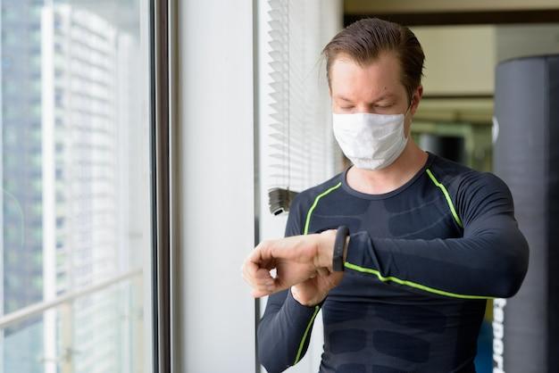 Молодой человек в маске для защиты от вспышки коронавируса проверяет умные часы и готов к тренировкам во время covid-19