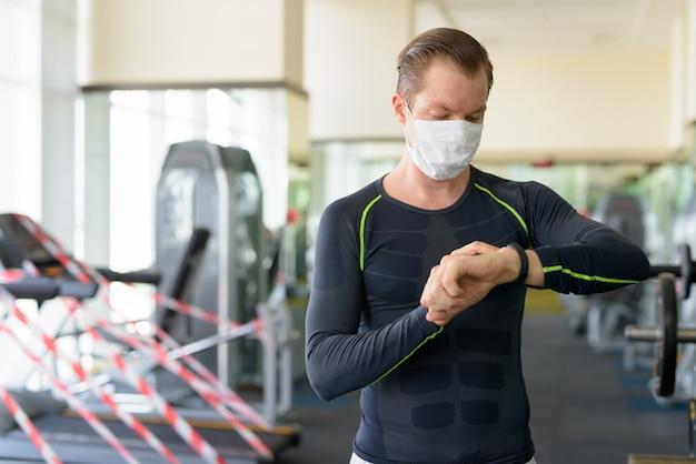 コロナウイルスcovid-19中にジムでスマートウォッチをチェックするコロナウイルスの発生からの保護のためのマスクを持つ若い男