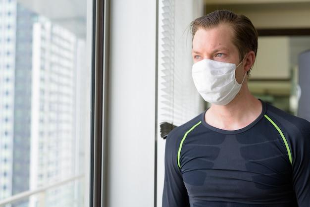 Covid-19の間に運動することを考えるコロナウイルスの発生からの保護のためのマスクを持つ若い男