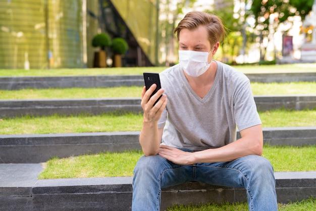 Молодой человек с маской для защиты от вспышки коронавируса, используя телефон, сидя на открытом воздухе
