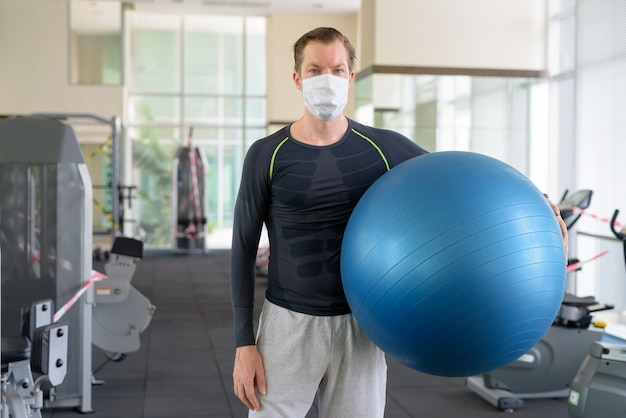 Young man with mask holding exercise ball at gym during coronavirus covid-19