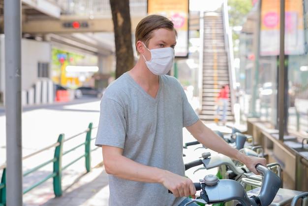 公共自転車サービスステーションでマスク駐車自転車を持つ若い男