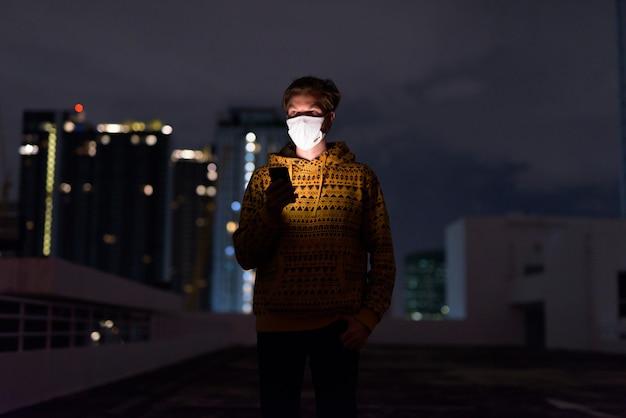 夜の街の景色に対して電話を使用しながらマスク思考と若い男