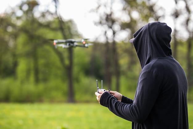 마스크를 가진 젊은 남자는 자연 경관에서 무인 항공기에 대한 원격 제어를 사용합니다.