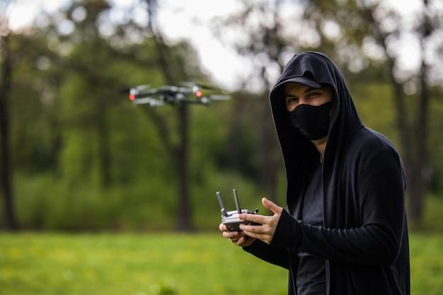 マスクを持つ若い男は森の中でドローンのリモコンを使用します