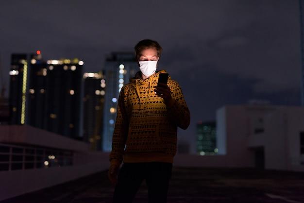 夜の街の景色に対して電話を使用してマスクを持つ若者