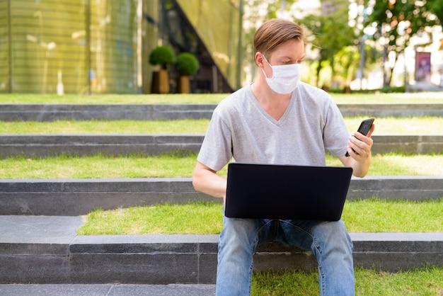 屋外に座っている間電話とラップトップを使用してマスクを持つ若者