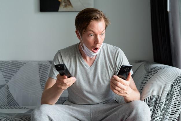 電話を使用して、検疫の下で自宅でテレビを見ながらショックを受けているように見えるマスクを持つ若い男