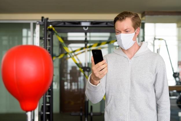 電話を使用してジムでボクシングの準備ができてマスクを持つ若い男