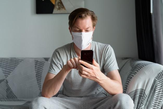 Молодой человек с маской, используя телефон дома в условиях карантина