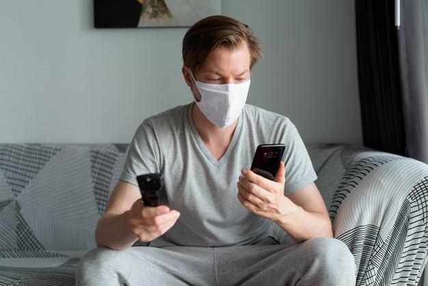 検疫の下で自宅でテレビを見ながら電話を使用してマスクを持つ若い男