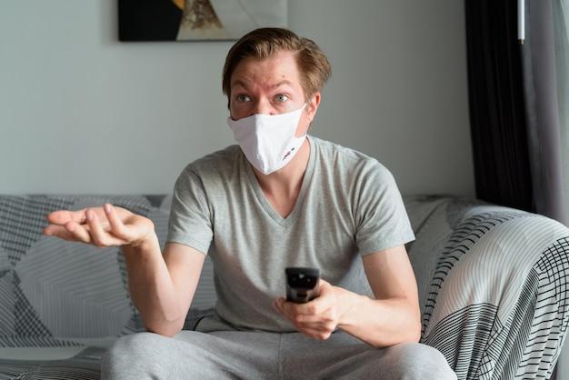 テレビを見て、検疫の下で自宅で混乱しているように見えるマスクを持つ若い男