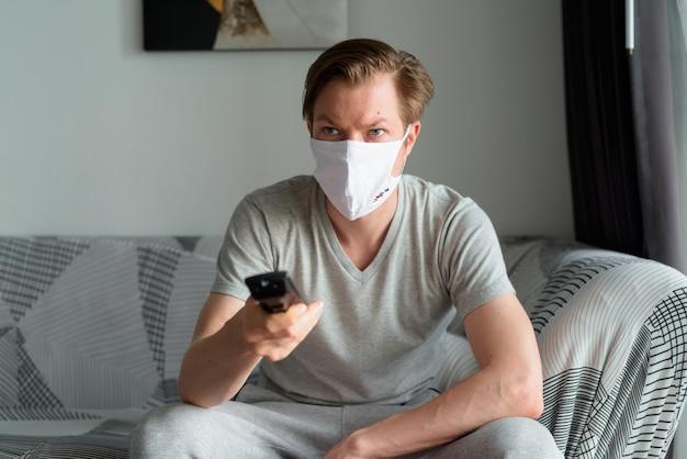 テレビを見て、検疫の下で家にいるマスクを持つ若い男