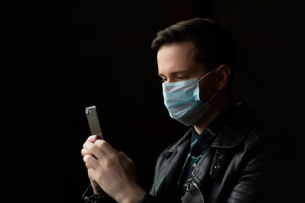 Young man with a medical face mask for protect covid-19 and in his hand is holding mobile phone