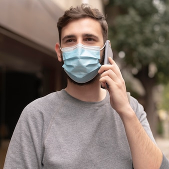 Young man with medical mask walking while talking on the phone