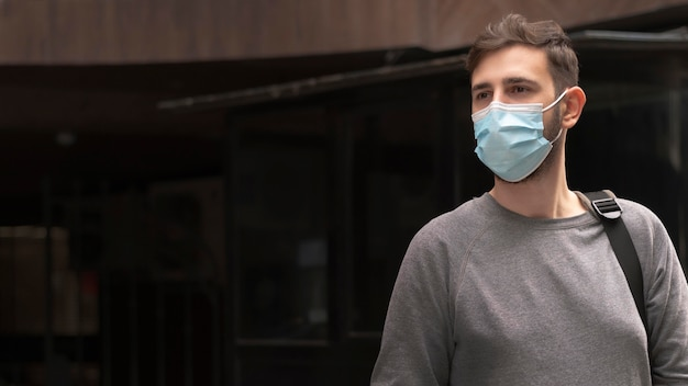 Young man with medical mask walking with copy space