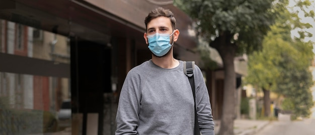 Young man with medical mask walking