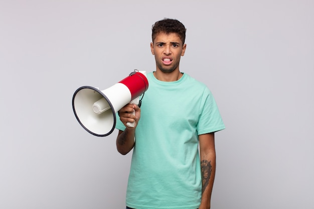 Young man with a megaphone feeling disgusted and irritated, sticking tongue out, disliking something nasty and yucky