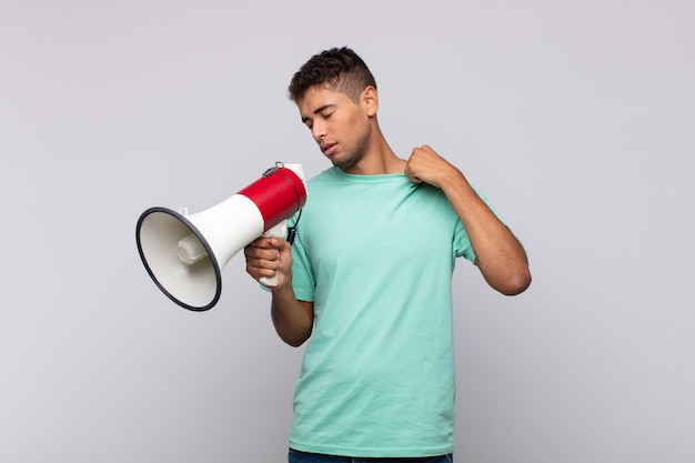 Young man with a megaphone feeling stressed, anxious, tired and frustrated, pulling shirt neck, looking frustrated with problem