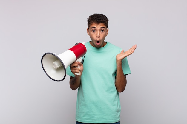 Young man with a megaphone looking surprised and shocked, with jaw dropped holding an object with an open hand on the side