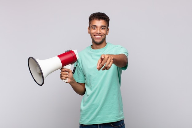 Young man with a megaphone pointing at camera with a satisfied, confident, friendly smile, choosing you