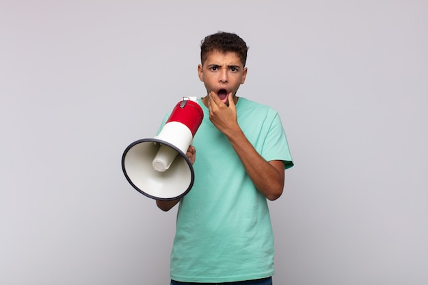 Young man with a megaphone with mouth and eyes wide open and hand on chin, feeling unpleasantly shocked, saying what or wow