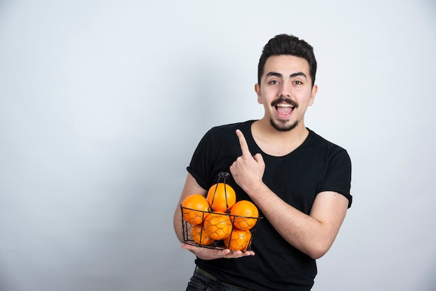 Young man with metallic basket full of orange fruits pointing up .