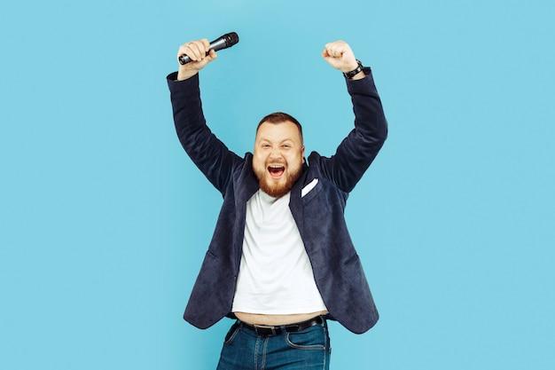 Молодой человек с микрофоном на синем фоне, ведущая концепция