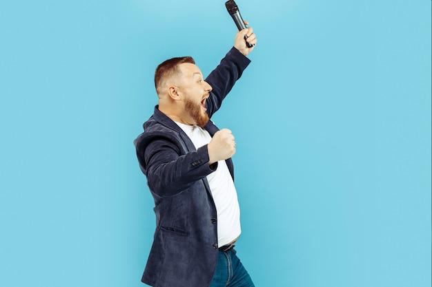 青色の背景、主要な概念にマイクを持った若い男